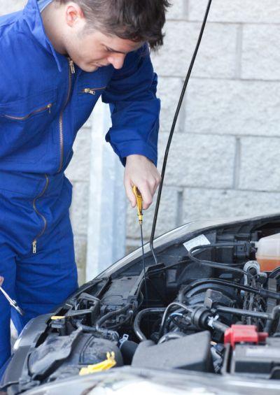 Mechanik sprawdza olej w silniku.